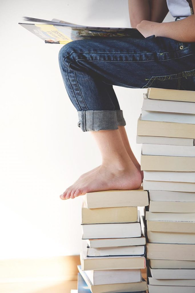 мотивация ребенка, девочка сидит на стопке книг и читает
