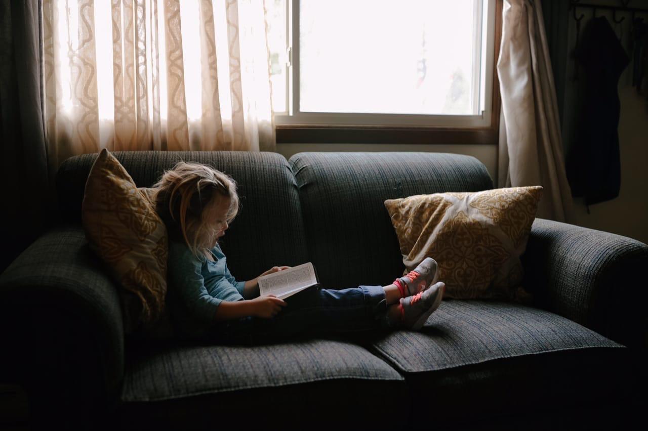 ребенок сидит на диване и сам занимается (читает)