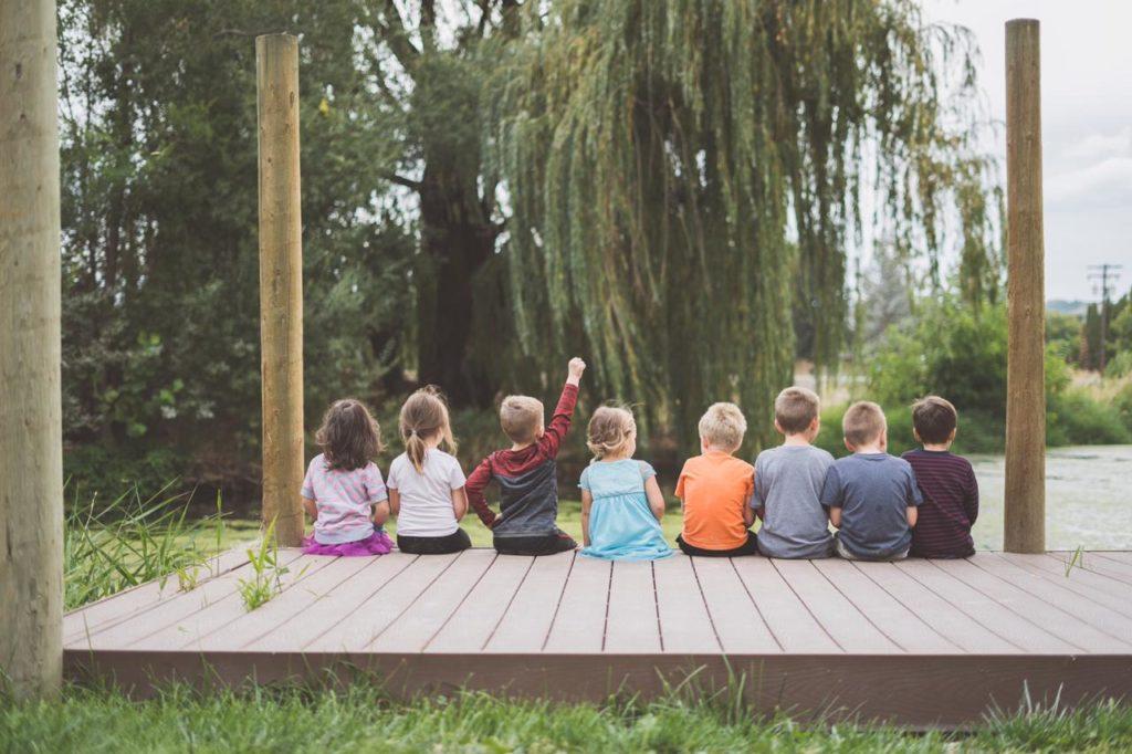 восемь детей сидят группой, один мальчик поднял руку вверх