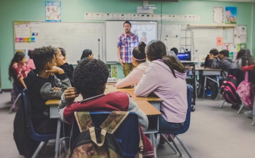 дети в школе сидят за партами, пока учитель объясняет урок, мотивация ребенка