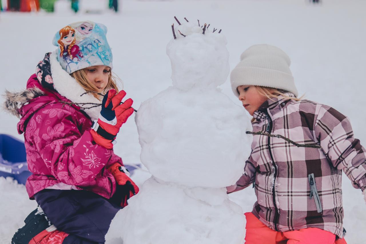 две девочки лепят снеговика